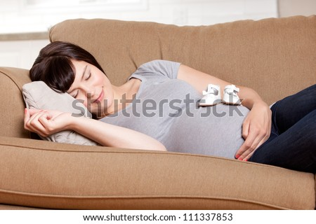 Content pregnant mother resting on sofa in living room with baby shoes on belly - stock photo