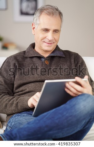 Contented attractive man relaxing at home on a couch using a tablet-pc balanced on his lap with a quiet smile - stock photo