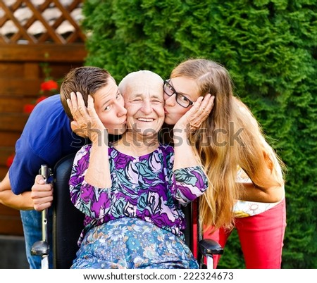 Contented grandmother being loved and  kissed by beautiful grandchildren. - stock photo