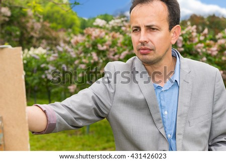 Conteplative middle-aged fashionable handsome male painter during painting on a sketchbook in a forest - stock photo
