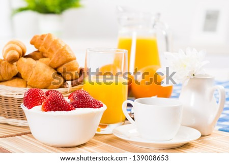 continental breakfast: coffee, strawberry and cream, croissant and juice - stock photo