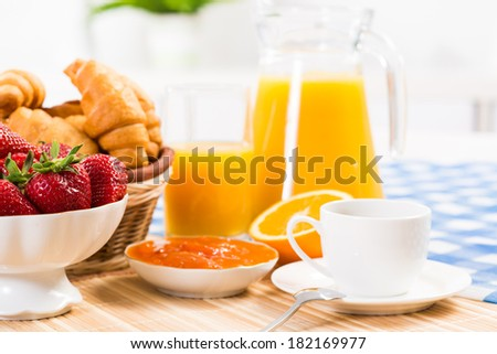 continental breakfast: coffee, strawberry, croissant and juice - stock photo