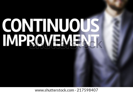Continuous Improvement written on a board with a business man on background - stock photo
