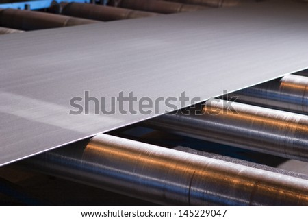 Continuous sheet of metallic material being fed through machine - stock photo