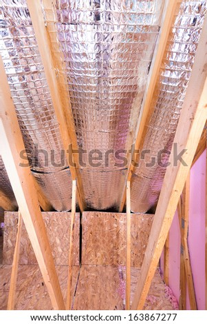 Continuous work of insulating of attic with reflective heat barrier between the attic joists and knee wall - stock photo