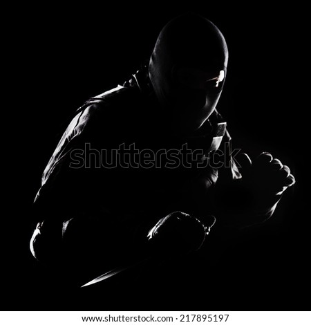 Contour shot of spec ops soldier with knife on black background - stock photo