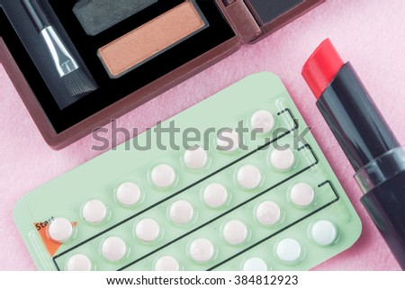 contraceptive pills and woman lipstick eye shadow - stock photo