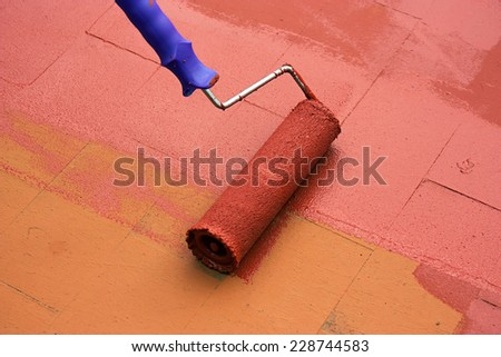Contract painter painting a floor on color red for waterproofing.  - stock photo