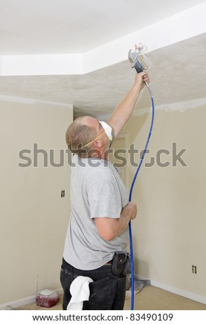 Contract painter updating colors of walls and painting ceilings bright white to speed up selling of home - stock photo