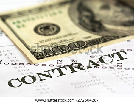 Contract wording on financial paper. Blurred one hundred dollar in the background - stock photo