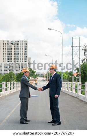 Contractor and client shaking hands on the background of road works - stock photo