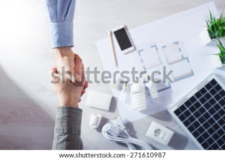 Contractor and customer shaking hands close up, energy saving CFL lamps, solar panel and house draft project on background, top view - stock photo