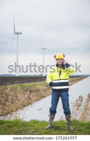 Contractor communicating in the field and calling his clients while he is standing in the grass with windmills in the background - stock photo