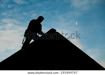 Contractor in Silhouette working on a Roof Top with blue Sky in Background - stock photo