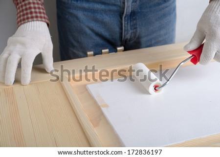 Contractor painting a wooden door - stock photo