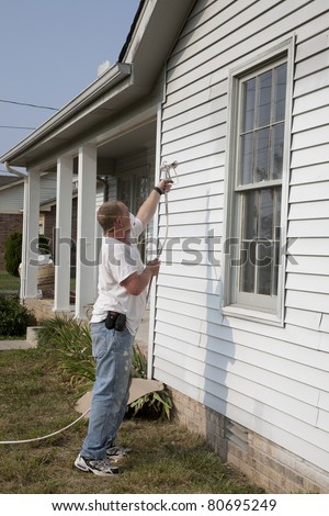 Contractor spray painting exterior of house, getting it ready for resale - stock photo