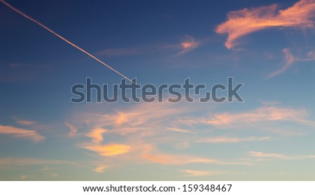 contrail in a blue and orange sky - stock photo
