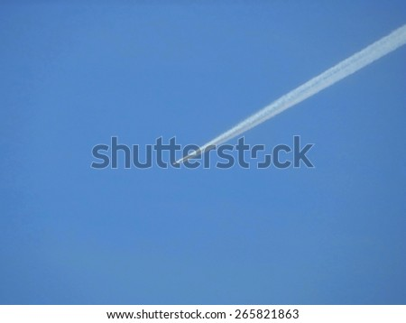 contrail of an airplane in the blue sky, blur - stock photo