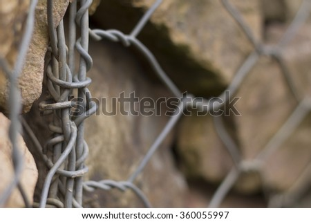 contrasting wrapped wire fence in front of stone wall. artistic limited focus and blur. room for text. - stock photo
