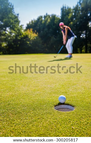 Contre-jour shot,The ball is about to drop in the hole. Close up on a winning swing by a pretty woman during a sunny day.  Focus on the ball rolling on the green grass. - stock photo