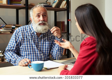 conversation between young student and senior bearded professor - stock photo