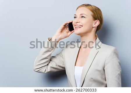 Conversation with pleasure. Beautiful young businesswomen talking on the mobile phone and smiling while standing against grey background - stock photo