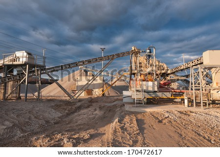 Conveyor of a gravel pit in the evening in front of cloudy sky - stock photo