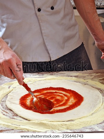 Cook adding tomato sauce on pizza dough. Cooking pizza. - stock photo
