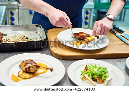 Cook are served at different dishes at the restaurant - stock photo
