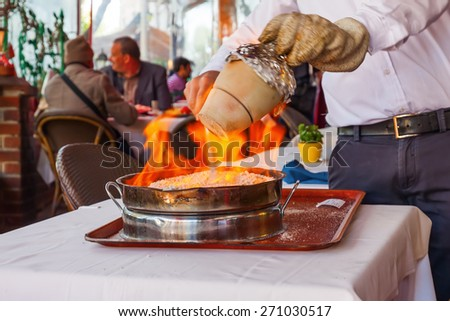 cook burns a traditional kebab dish in an earthenware vessel on the restaurant table in Istanbul, Turkey - stock photo