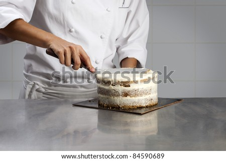 Cook coating a cake with cream - stock photo