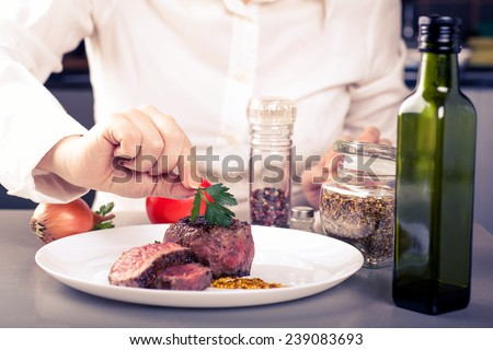 cook completes the dish of medallions, are nearby spices - stock photo