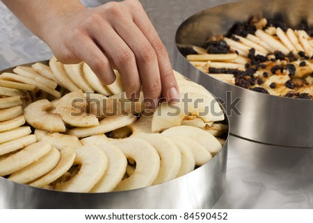 Cook filling the rest of the cake mold with the sliced apples - stock photo