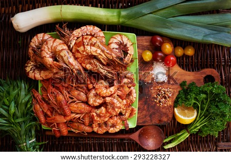 Cook fish restaurant has prepared a snack for beer, shrimp Royal, Tiger prawns, crabs, all laid out on a bright contrast dish served with lemon wedges, cherry tomatoes and parey for fresh spring salad - stock photo