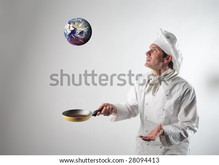 Cook flipping planet earth with pan - stock photo