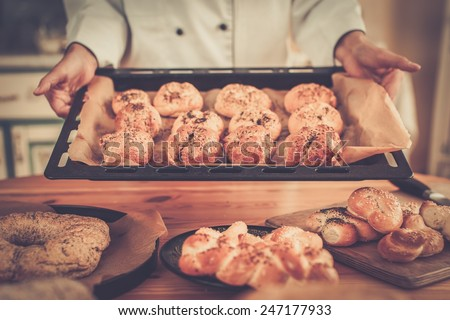 Cook hands holding baking tray with homemade baked goods - stock photo