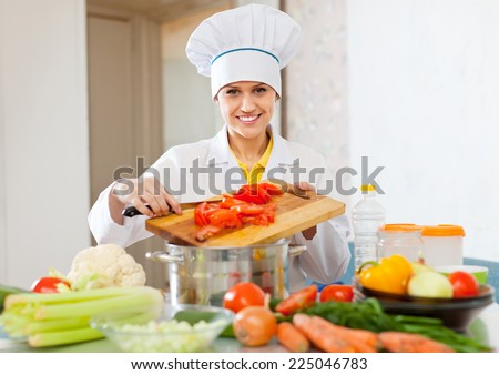 cook in toque works with tomato and other vegetables at commercial kitchen   - stock photo