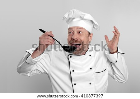 cook in white hat tasting the cooked them food - stock photo