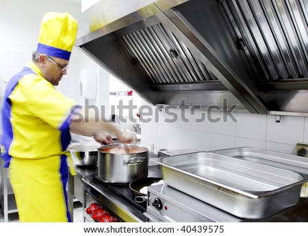 cook is stirring a dish in a restaurant kitchen - stock photo
