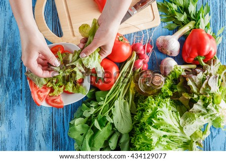 Cook is tearing lettuce while making fresh summer salad, closeup shoot - stock photo