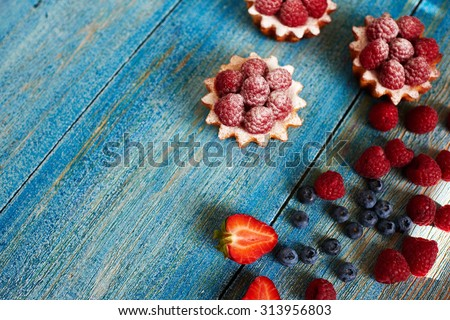 Cook Italian bakery prepare light mouth-watering diet of pastry basket of unleavened dough with fresh raspberries, sprinkle them with powdered sugar - stock photo