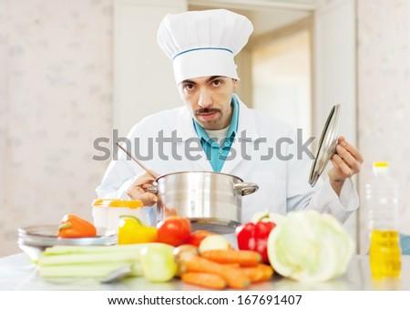 cook man cooking vegetarian soup at kitchen - stock photo