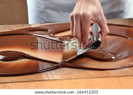 Cook mixing chocolate cream with professional chocolate spatula. Melted dark chocolate. - stock photo