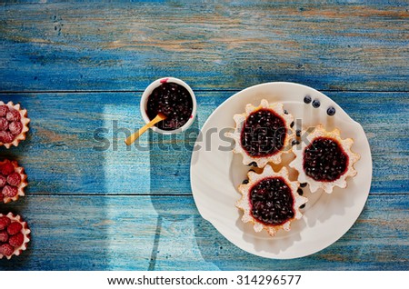 Cook prepared tarts made from unleavened dough, filled them with different fillings are several tartlets on a plate with berry jam - stock photo