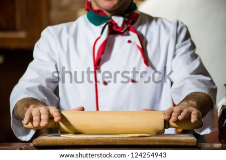 Cook rolls out the dough on a board, the traditional cooking - stock photo