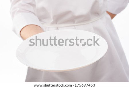 Cook's hand holding an empty plate on white background - stock photo