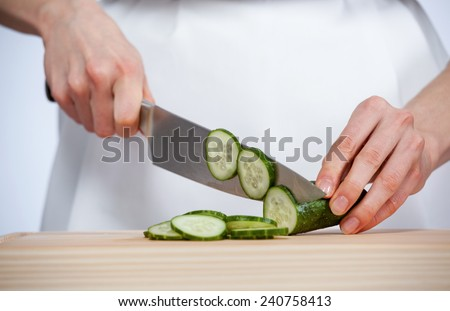 Cook's hands cutting fresh cucumber on wooden board - stock photo