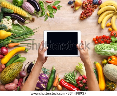 Cook's hands holding a touch screen tablet close up, kitchen table with food ingredients, Healthy food background, top view. High resolution product, - stock photo