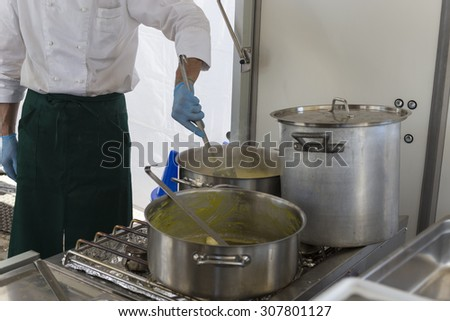 cook stirring risotto milanese with safran - stock photo