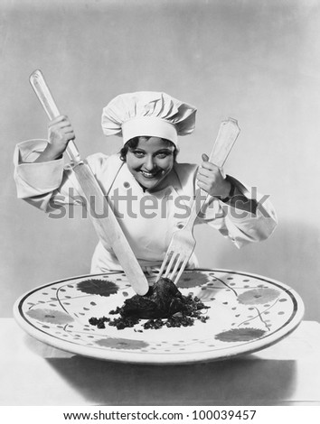 Cook with food on oversize plate with oversize utensils - stock photo